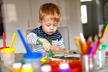 Three year old boy busy painting at home, with paint pots and brushes, Scotland, United Kingdom
