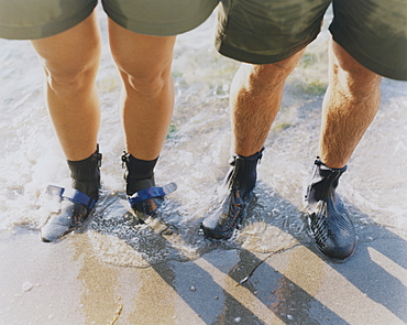 Man and woman wearing waterproof booties, standing in surf, Washington, United States