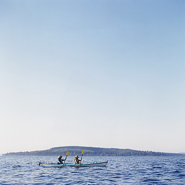 Middle aged man and woman sea kayaking on calm water, Washington, United States