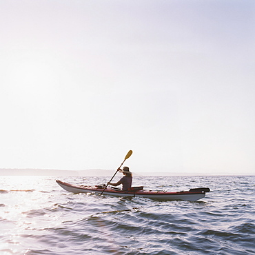 Middle aged woman sea kayaking at duskcan, Washington, United States