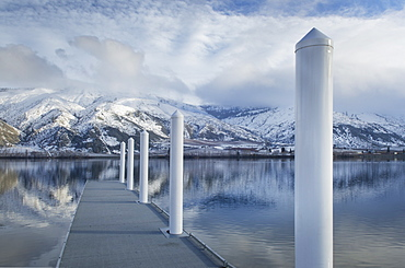 Pillars on dock at lake near snow covered mountain range, Washington, United States