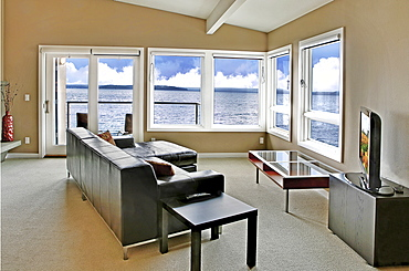 A living room in a waterfront house, with a large window and an ocean view, Washington, United States