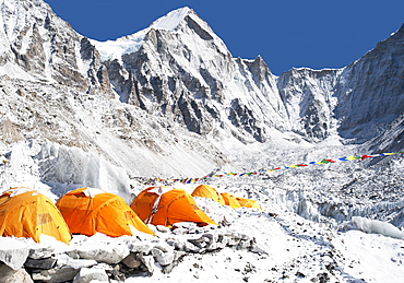 A group of orange tents at a climbers base camp in the Himalayas region, Khumbu region, Nepal