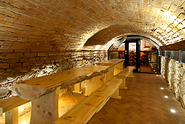 Climate controlled wine cellar, with a domed brick ceiling and walls, stacked benches, Estonia