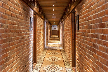 A hotel with old fashioned retro styled rooms, and rustic objects, corridor with patterned carpet, room doors, Estonia