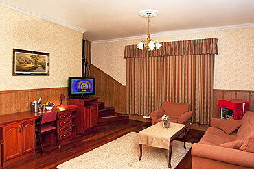 A hotel with old fashioned retro styled rooms, and rustic objects, sofa and chairs and television, Estonia