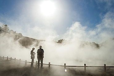 Two people in rising mist at a thermal pool site, Rotorua, North Island, New Zealand