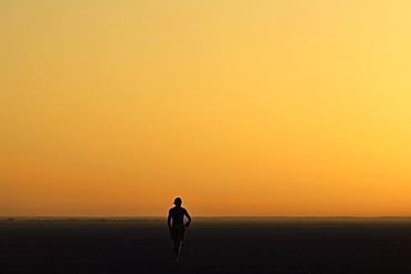 Person walking across the Makadikadi Salt Pans in Botswana, at sunset