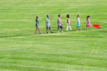 A group of children walking up a sloping path in height order following the smallest one at the front with a red wheelbarrow, Utah, USA