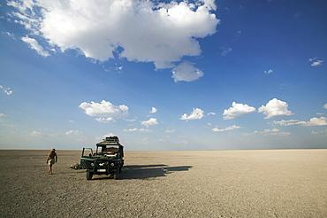 Man walking past 4x4 parked on the Makadikadi Salt Pans in Botswana