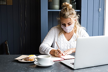 Woman wearing face mask sitting alone with a laptop, writing in note book, working remotely, Watlington, Oxfordshire, United Kingdom