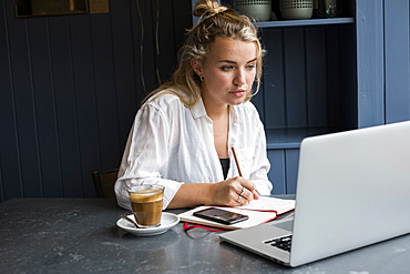 Woman sitting alone at a cafe table with a laptop computer, writing in note book, working remotely, Watlington, Oxfordshire, United Kingdom