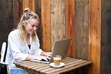 Young blond woman sitting alone at a cafe table with a laptop computer, working remotely, Watlington, Oxfordshire, United Kingdom