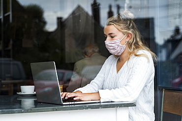 Woman wearing face mask sitting alone at a cafe table with a laptop computer, working remotely, Watlington, Oxfordshire, United Kingdom