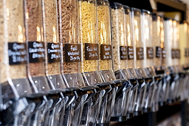 Close up of food dispensers with dried pasta in a waste free wholefood store, Watlington, Oxfordshire, United Kingdom