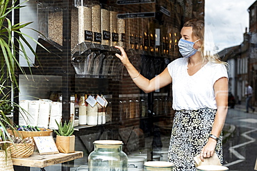 Woman wearing face mask shopping in waste-free local store, sustainability, Watlington, Oxfordshire, United Kingdom