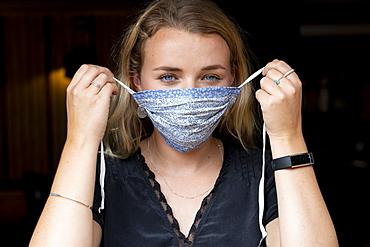 Portrait of young blond woman putting on blue face mask, Watlington, Oxfordshire, United Kingdom