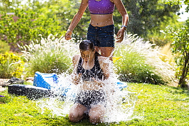 Two teenage girls wearing swimwear playing with water balloons in a garden, New Mexico, United States
