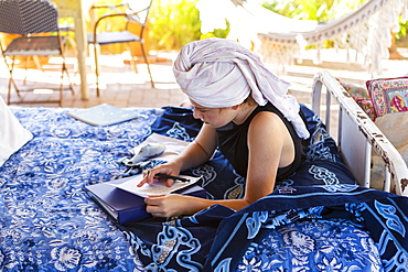 Teenage girl with hair wrapped in towel sitting on outdoor bed, doing homework, New Mexico, United States
