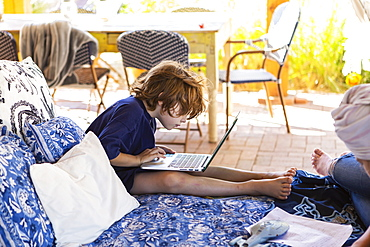 Boy with brown hair sitting on outdoor bed, doing homework on laptop, New Mexico, United States