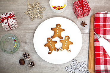 High angle close up of Christmas presents, decorations and Gingerbread Men on a white plate