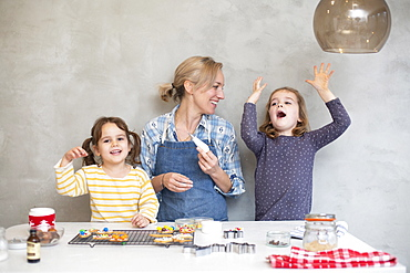 Blond woman wearing blue apron and two girls baking Christmas cookies