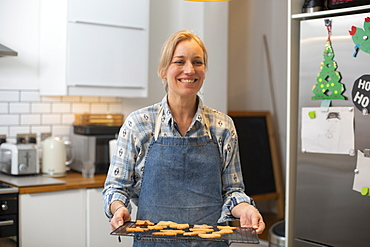 Blond woman standing in kitchen, holding tray with Christmas cookies, smiling at camera