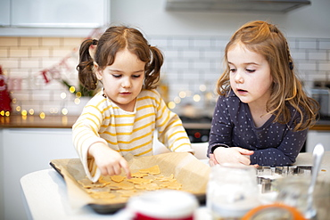 Two girls standing in kitchen, baking Christmas cookies