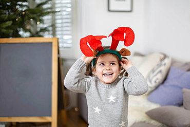Smiling young girl wearing grey jumper putting on reindeer antler headband