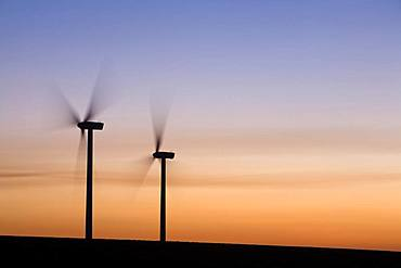 Two wind turbines turning, sunset sky, United States of America