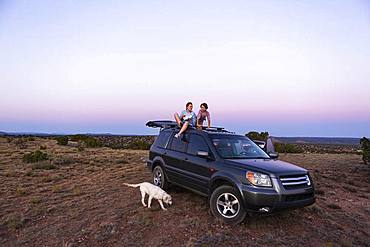 Teenage girl and her younger brother sitting atop their SUV at sundown