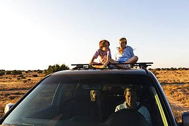 Teenage girl and her younger brother  on top of SUV on desert road, New Mexico, United States of America