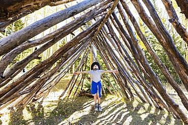 Young boy looking up, standing in a tunnel made of tree logs