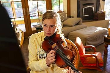 teenage girl plucking strings of her violin at home