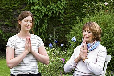Woman and female therapist seated in a garden, hands together and eyes closed