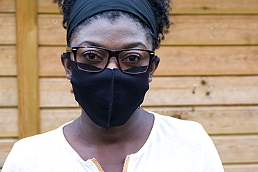 Portrait of black woman wearing glasses and face mask, looking at camera