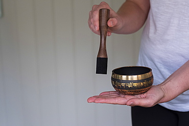 female therapist using Tibetan singing bowl, sound therapy
