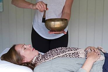 Woman on a couch, and a female therapist using Tibetan singing bowl, sound therapy