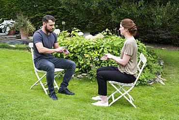 Man and female therapist engaged in alternative therapy session in a garden