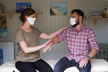 Therapist and client in face masks, touching with arm outstretched