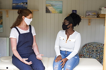 Woman and female therapist in face masks at a therapy session