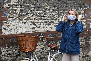 Young blond woman standing next to bicycle with basket, putting on face mask, Oxfordshire, England, United Kingdom