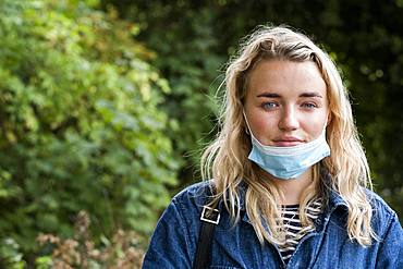 Portrait of young blond woman wearing face mask, looking at camera, Oxfordshire, England, United Kingdom
