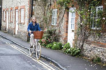 Young blond woman cycling down a village street, Oxfordshire, England, United Kingdom