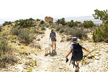 children hiking on Chimney Rock trail, through a protected canyon landscape, New Mexico, United States of America