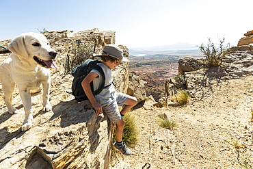 young boy hiking with his dog on Chimney Rock trail, through a protected canyon landscape, New Mexico, United States of America