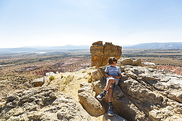 Boy hiking to the top of Chimney Rock landmark in a protected canyon landscape, New Mexico, United States of America