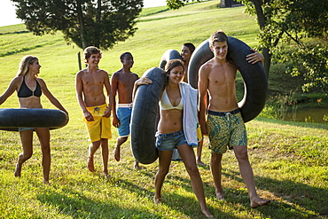 A group of young people, boys and girls, holding towels and swim floats, going for a swim, Maryland, USA