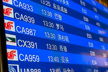 Close-up of departure board in airport terminal, Beijing, China, China