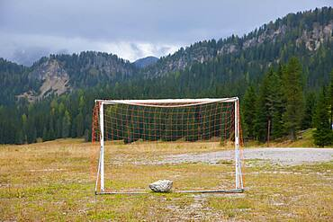 Soccer goal and a flat field in a valley in the Dolomites, South Tyrol, Italy